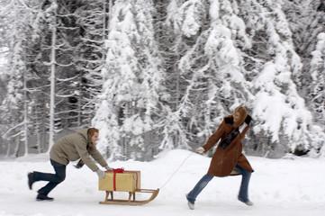 Junges Paar mit Schlitten und Weihnachtsgeschenk, Seitenansicht