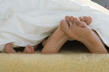 Füße von Baby und Eltern schauen aus dem Bett