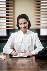 Charming vintage receptionist working at office desk