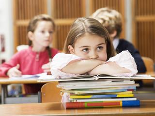 Mädchen sitzen Schreibtisch, stützen sich auf Stapel Bücher