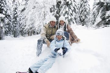 Österreich, Salzburger Land, Junge mit seiner Familie im Schnee