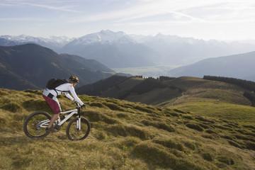 Österreich, Salzburger Land, Zell am See, Frau fährt Mountainbike