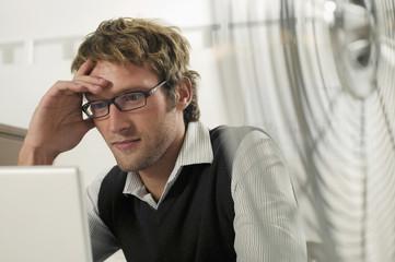 Junger Mann arbeitet am Laptop