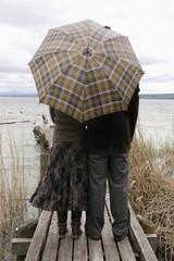 Paar am Steg mit Regenschirm, Rückansicht