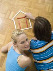 Paar auf dem Boden liegen, Gebäude Haus mit Stiften