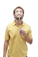 Junger Mann mit Joghurt,balanciert Löffel auf Nase, Portrait
