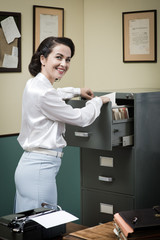 Smiling secretary searching files in the filing cabinet