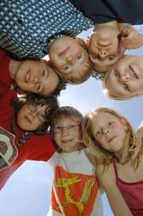 Kinder formen einen Kreis, schauen nach unten in die Kamera, Kameradschaft
