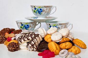 Набор чашек и много сладостей на белом фоне