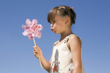 Mädchen pustet kleines Windrad an