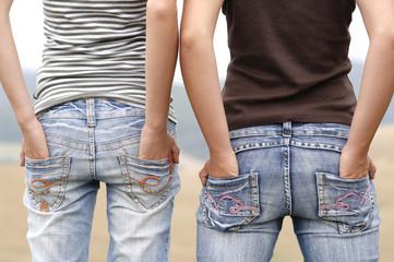 Zwei Mädchen mit den Händen in den Gesäßtaschen, Jeans, Po