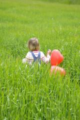 kleines Mädchen hält Luftballons, spazieren gehen in Wiese, Rückansicht
