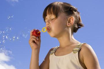 Mädchen macht Seifenblasen, die Augen geschlossen