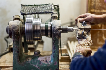 worker hands using woodturning lathe tool and industry tools