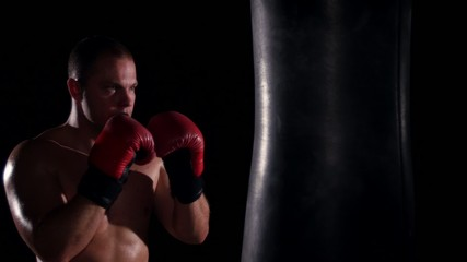 boxer man during boxing hiting heavy bag at training fitness gym