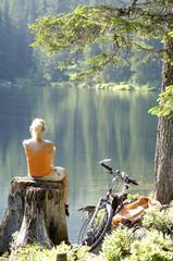 Junge Frau sitzt auf Baumstamm, Rückansicht