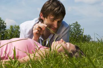 Junges Paar in der Wiese, Mann hält Grashalm