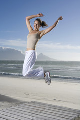 Südafrika, Kapstadt, Junge Frau springt am Strand