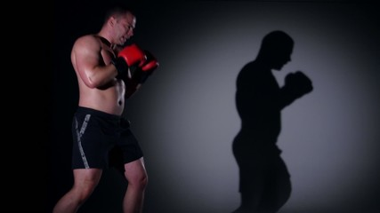 Boxer training shadow boxing over black background