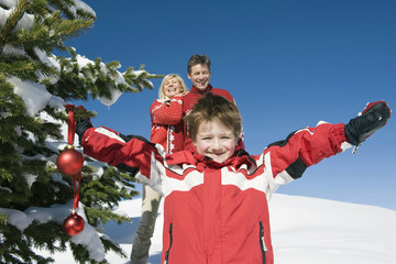 Italien, Südtirol, Seiseralm, Junge halten Christbaumkugeln, Eltern, Portrait