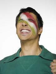 Fußballfan mit mexikanischer Flagge, gemalt auf Gesicht