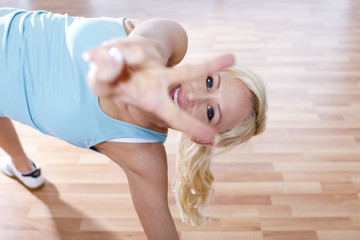 Deutschland, Frau entspannt im Fitness-Studio, lächelnd