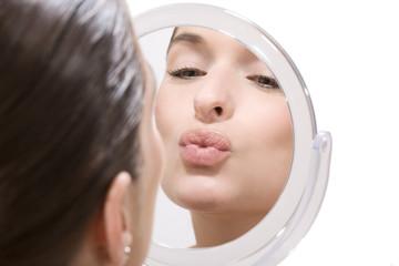 Junge Frau macht Kussmund vor Spiegel