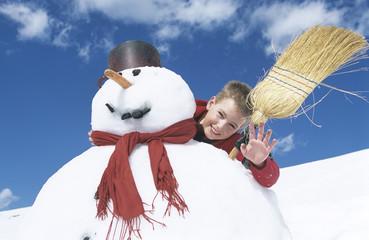 Junge steht hinter Schneemann mit Besen
