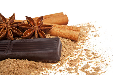 Cinnamon sticks, chocolate and anise on a white background