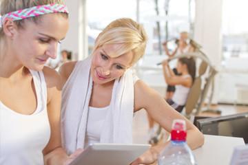 Deutschland, Frauen erfrischen sich nach dem Training im Fitness-Studio, lächelnd