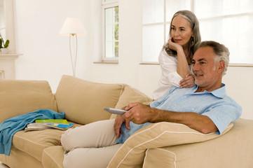 Ehepaar in Wohnzimmer, Mann mit Fernbedienung