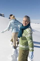 Italien, Südtirol, Seiseralm, drei Personen spazieren im Schnee