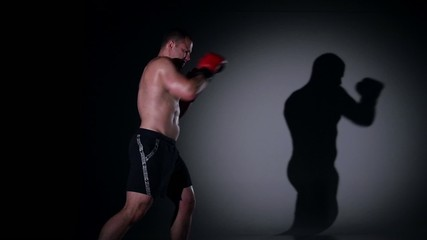Boxer training shadow boxing over black background. Slow motion.
