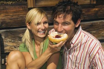Österreich, Salzburger Land, glückliches Paar isst Brötchen