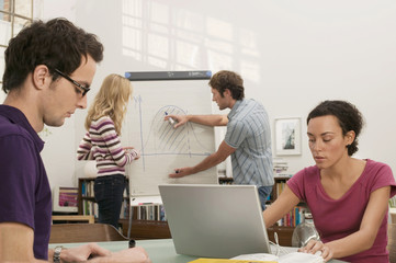 Frau jung arbeiten am Laptop, Mann erklären Grafik um eine Frau