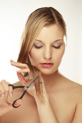Junge Frau mit Schere schneidet sich die Haare
