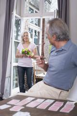 Älterer Mann spielt Solitär, ältere Frau steht in der Tür mit Blumen, Portrait