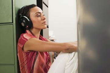 Junge Frau sitzt auf dem Boden, mit Kopfhörern, die Augen geschlossen