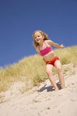 Deutschland, Ostsee, Mädchen(6-7) springt von einer Düne