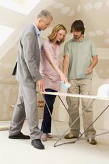 Junges Paar und Architekten auf der Baustelle