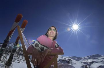 Junge Frau sitzt auf Liegestuhl im Schnee, Flachwinkelansicht