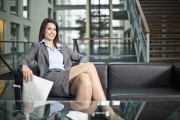Deutschland, Bayern, Geschäftsfrau mit Zeitung, Lächeln, Portrait