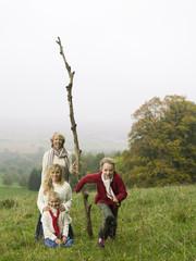 Deutschland, Großmutter mit Enkelinnen in der Landschaft, halten Zweig