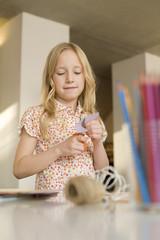 Mädchen (8-9) bastelt, Schneidet Papier mit einer Schere