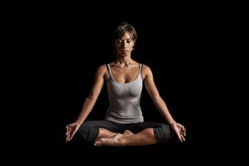 woman practicing yoga meditation on black background