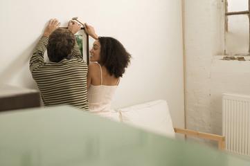 Junges Paar hängt Bild auf Bild, Rückansicht