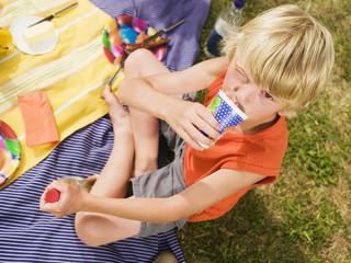 Junge trinkt aus Pappbecher, Portrait