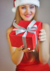 Woman holding out red Christmas gift on the palm of her hand