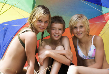 Junge und Mädchen sitzen unter Sonnenschirm