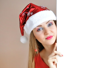 Beautiful christmas woman in Santa Claus hat with signboard